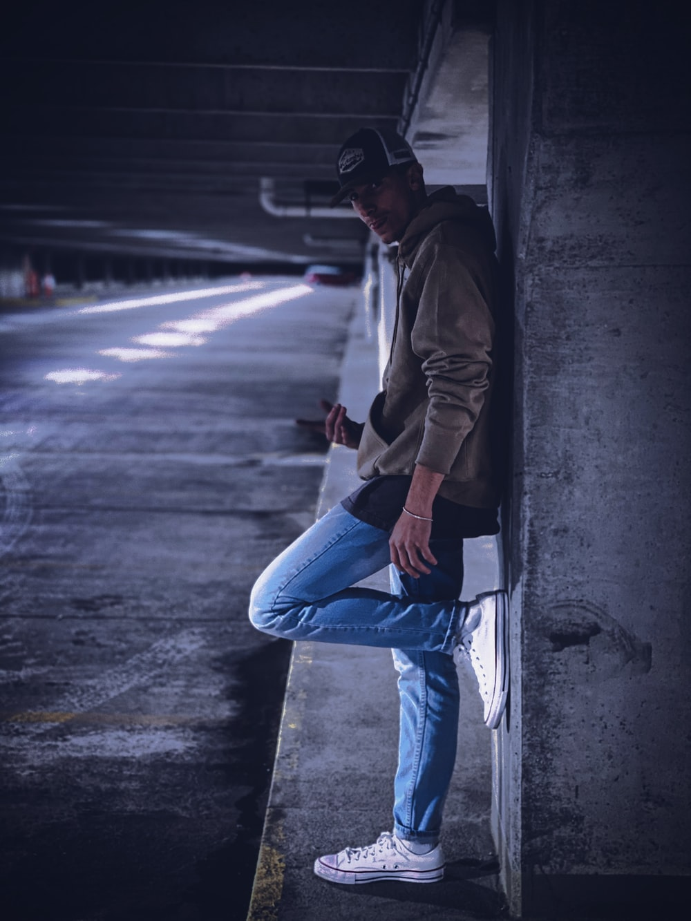 man in brown jacket and blue denim jeans sitting on concrete wall during daytime