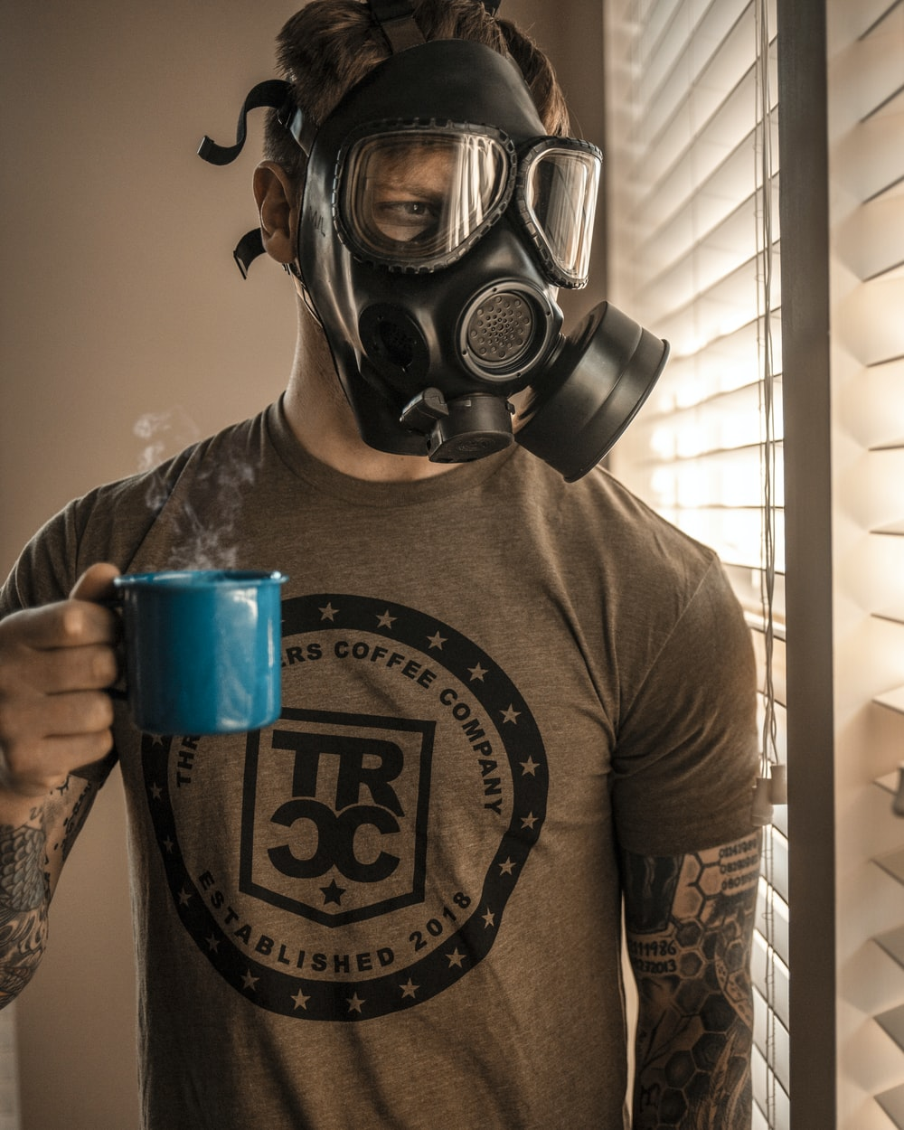 man in gray and black crew neck shirt wearing gas mask holding blue plastic cup