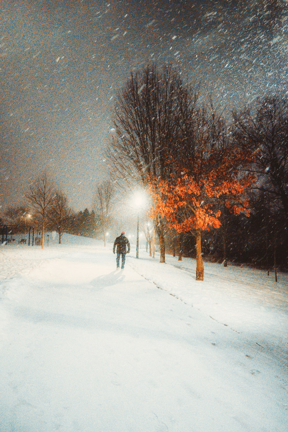 person walking on snow covered road during night time