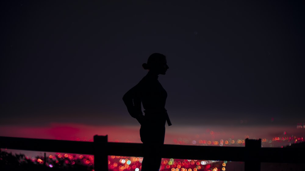 silhouette of man standing on bridge during night time