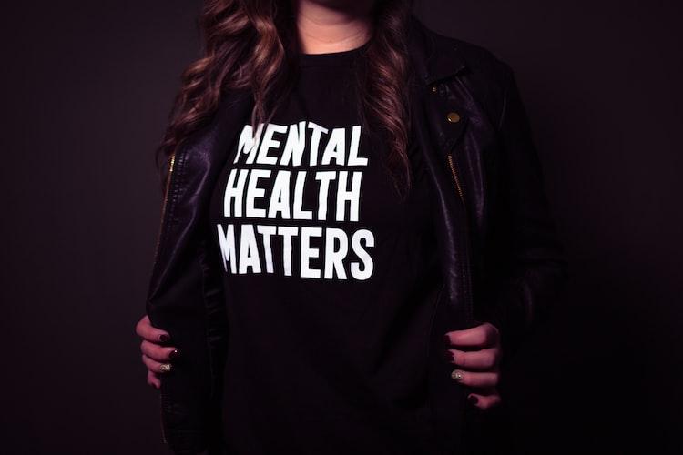 """Ragazza con una maglia nera con la scritta """"mental Health matters"""""""