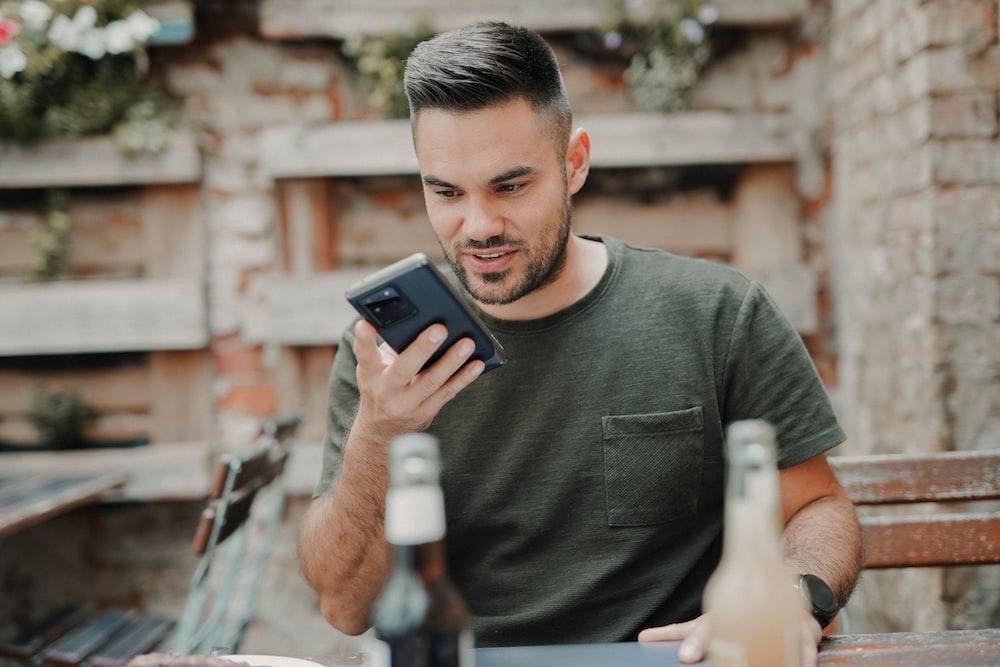 man in gray crew neck long sleeve shirt holding black smartphone