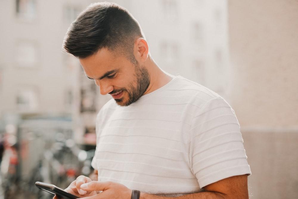 man in white crew neck t-shirt using smartphone