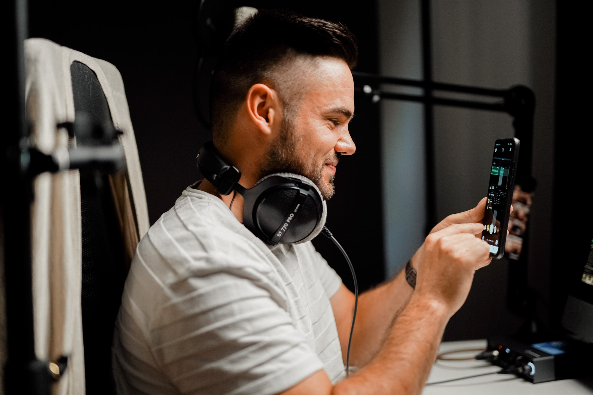 Man recording an instagram story with headphones in front of a smartphone with podcast gear like headphones, an interface and a microphone stand.