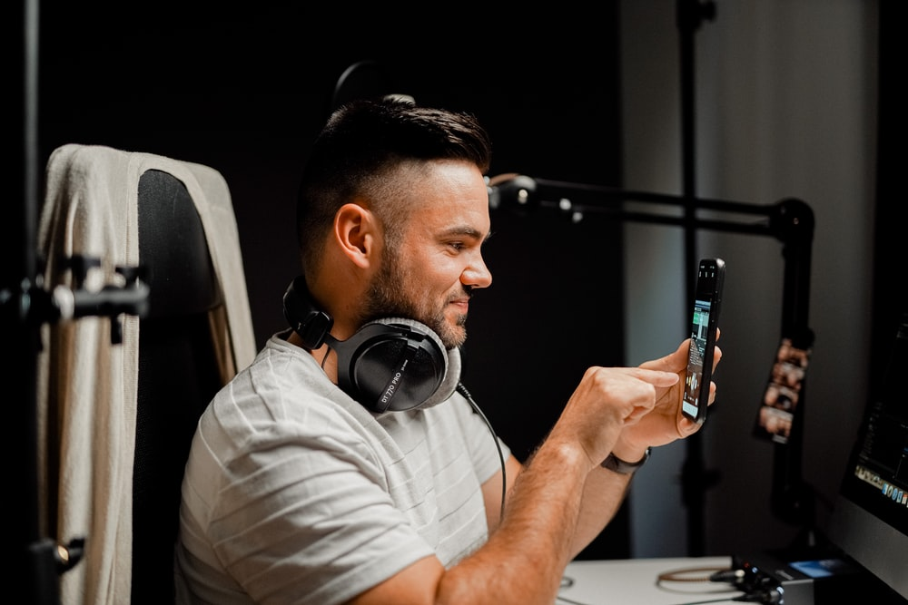 man in white crew neck t-shirt wearing black headphones holding smartphone