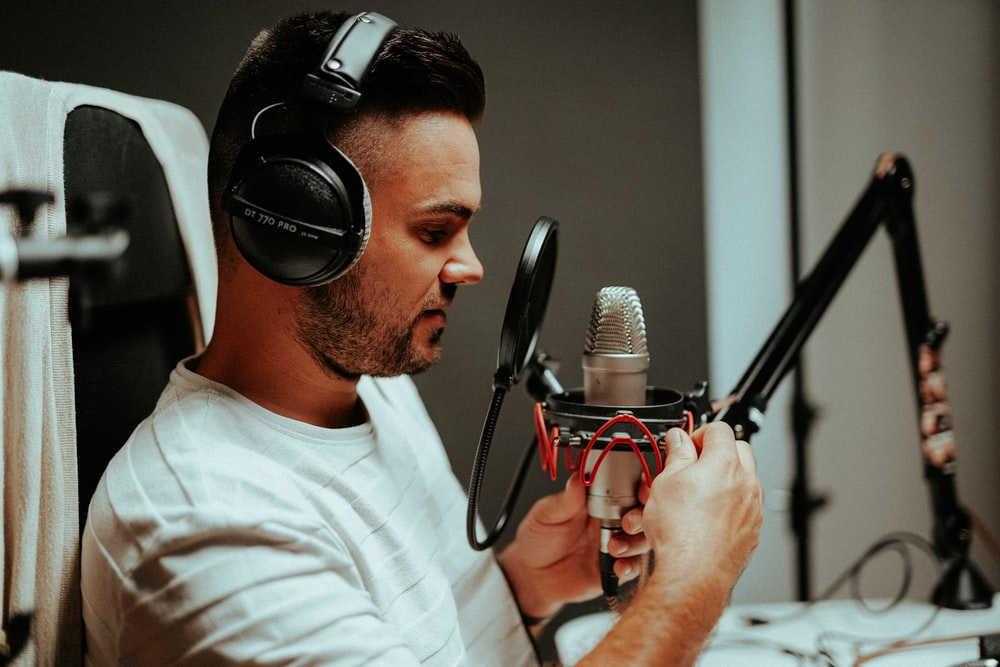 man in white crew neck t-shirt holding microphone
