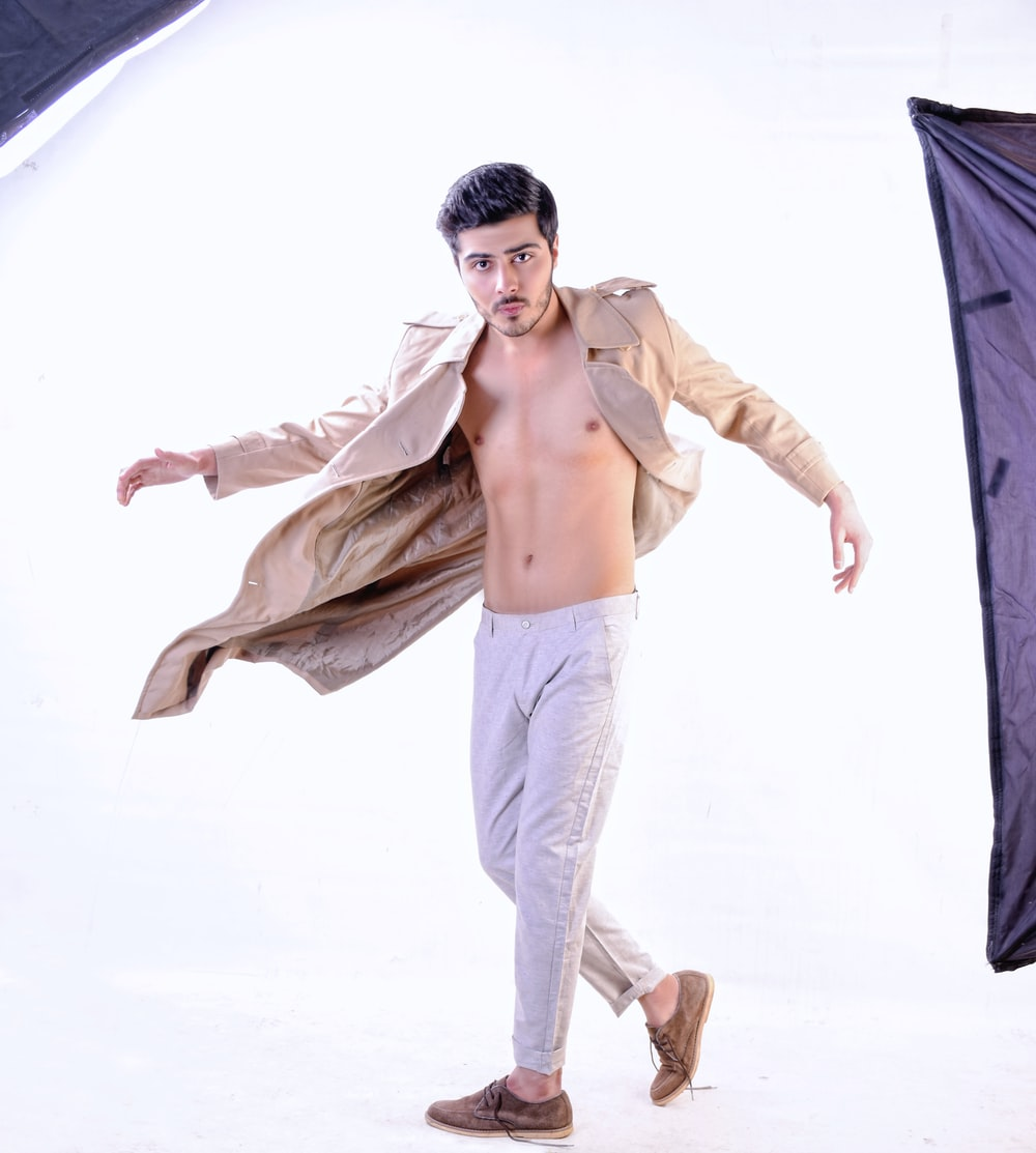 topless man in white pants holding black textile