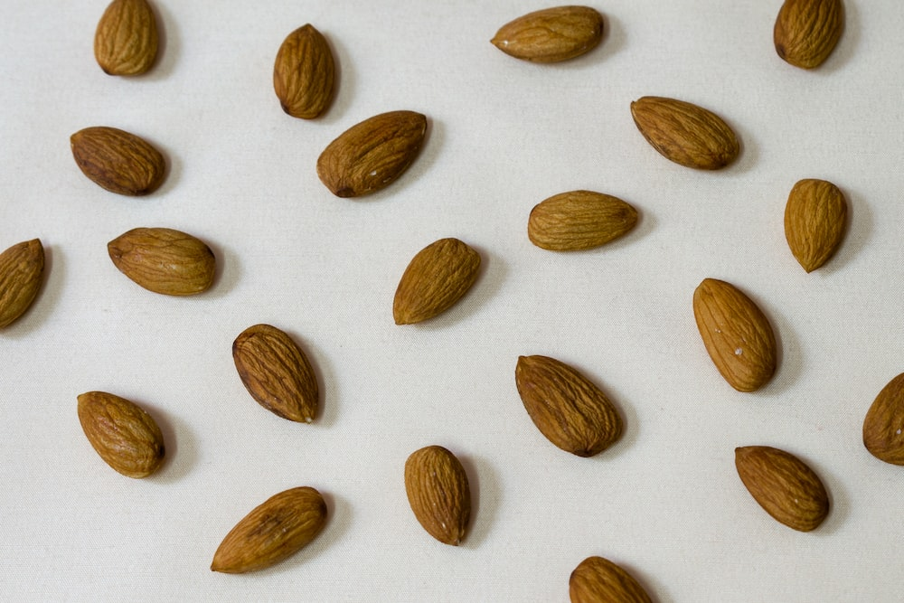 brown almond nut on white surface