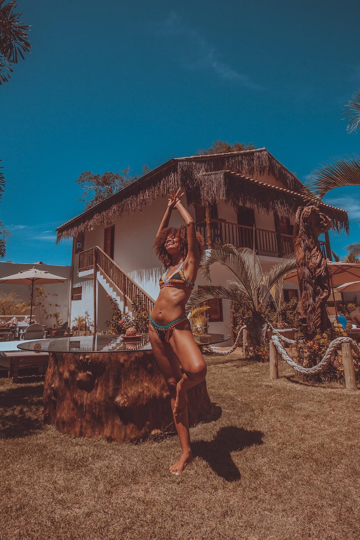 woman in black bikini standing on brown sand during daytime