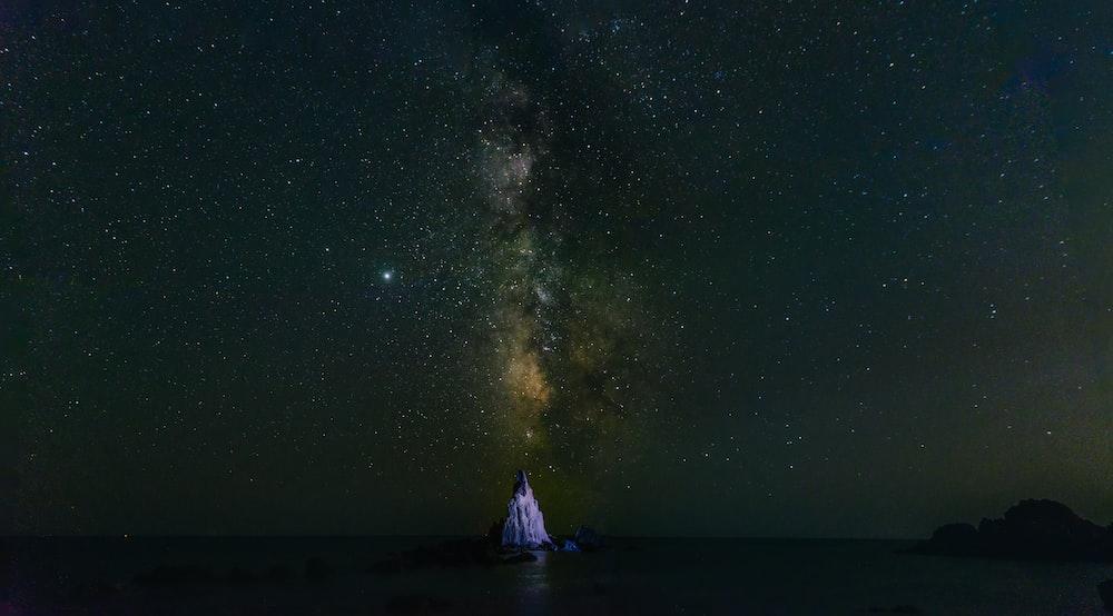 boat on sea under starry night