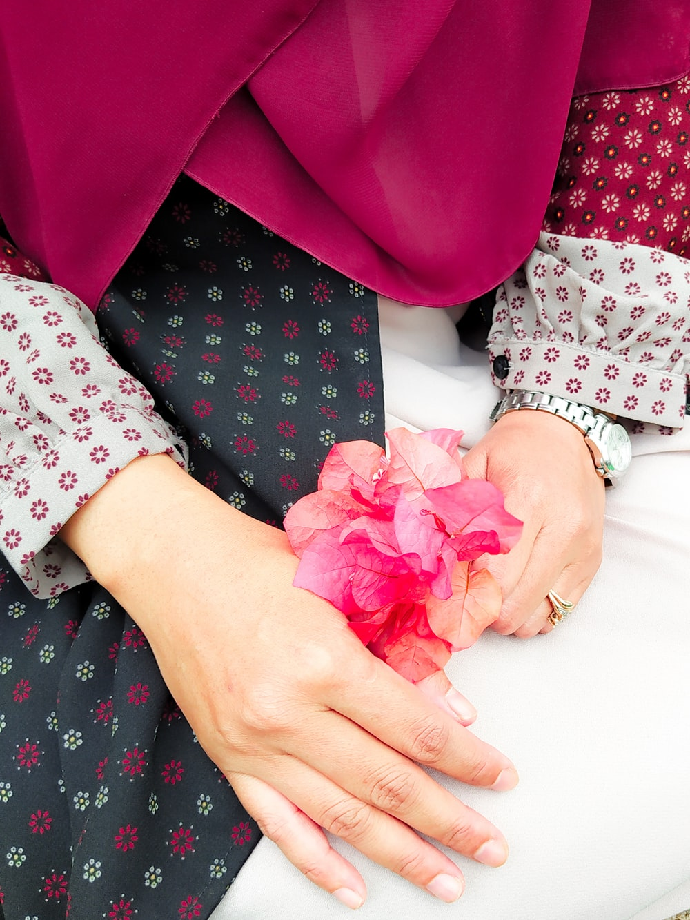 person holding pink flower petals