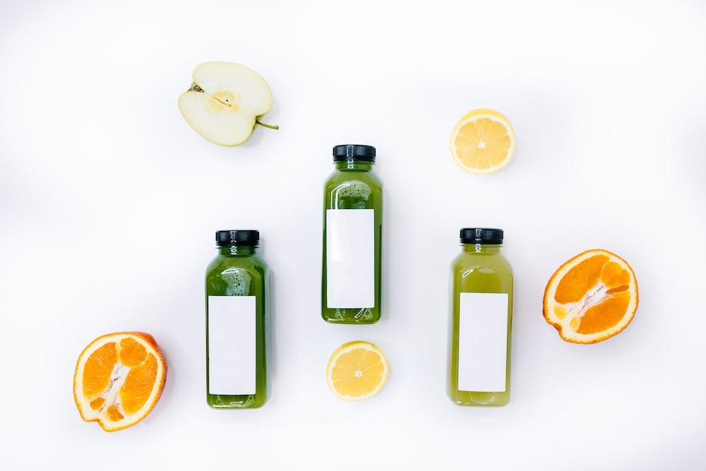 3 bottles with sliced lemon and sliced orange fruits
