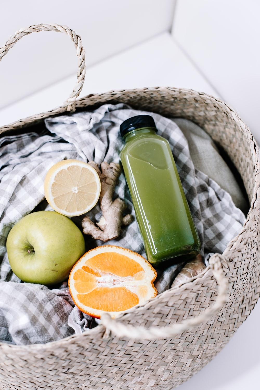 green disposable lighter beside orange fruit on brown woven basket