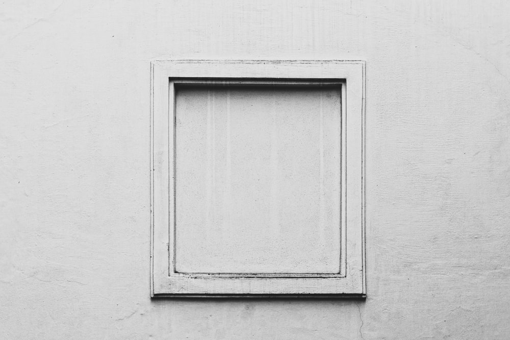 white wooden door on gray concrete wall