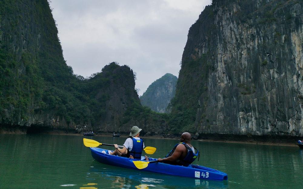 man in blue life vest riding blue kayak on river during daytime
