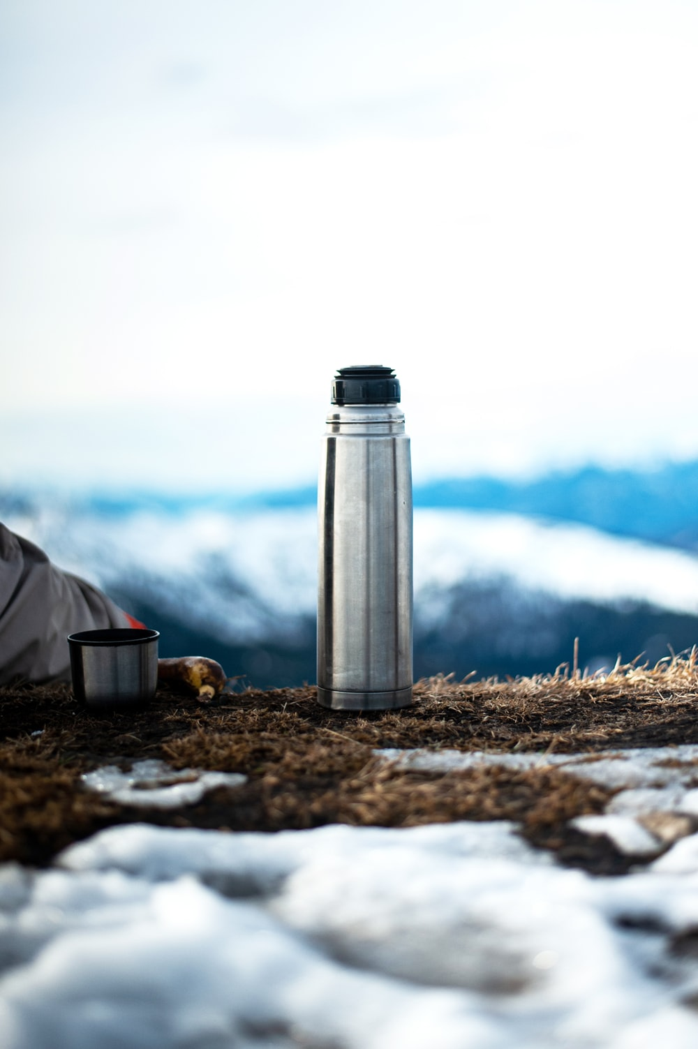 silver vacuum flask on brown dried grass