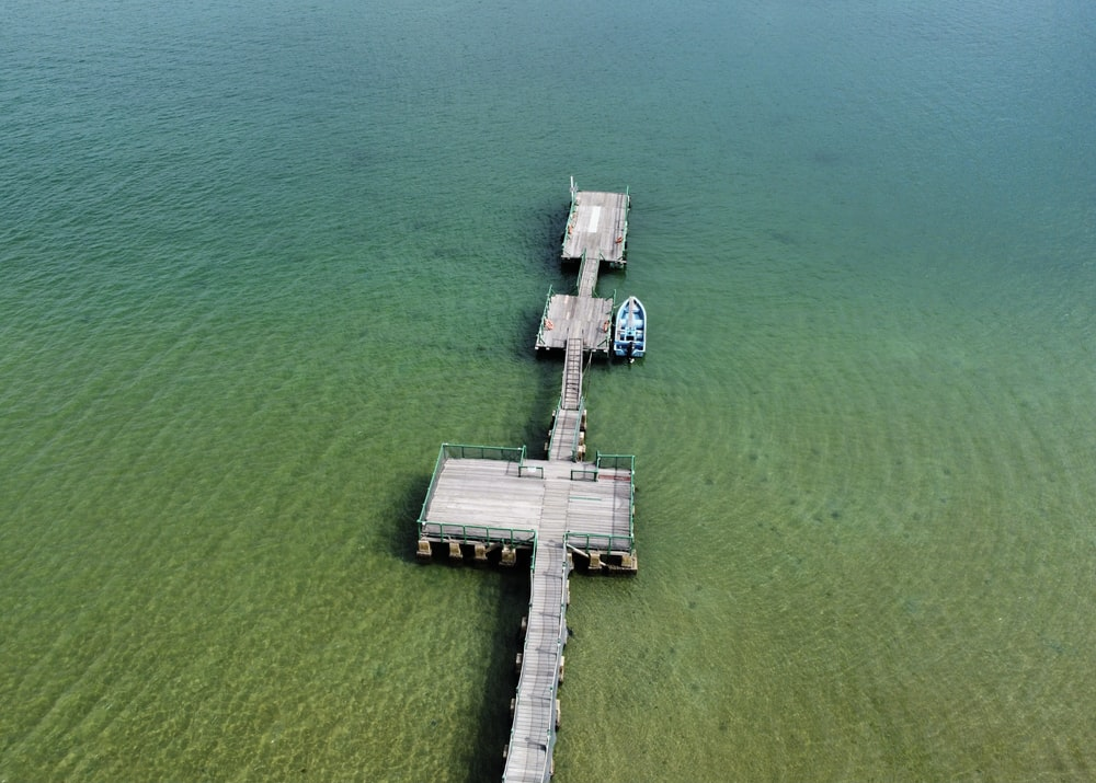 aerial view of white wooden dock on body of water during daytime