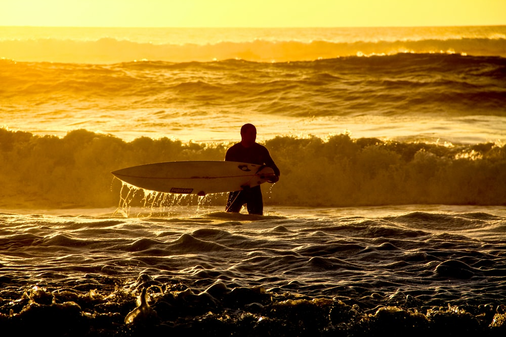 man in black wet suit holding white surfboard on sea waves during daytime