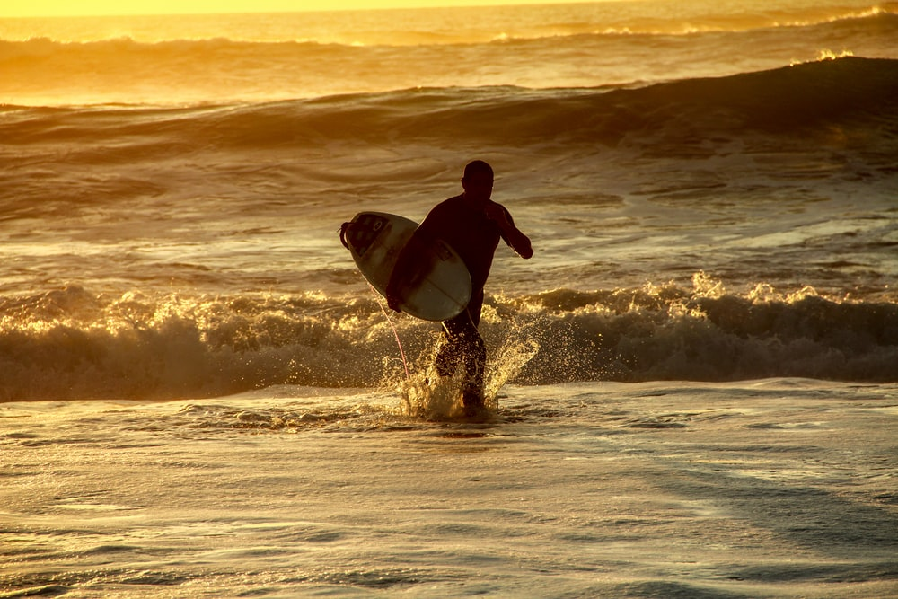 man in black wetsuit surfing on sea waves during sunset