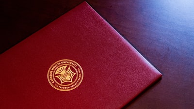 red and gold book on black textile diploma teams background