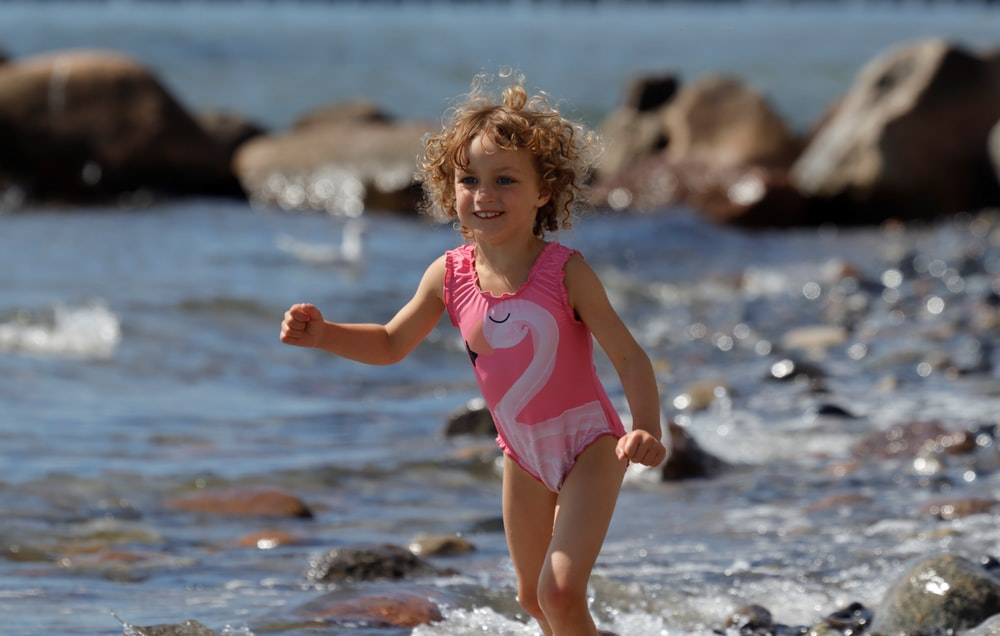 girl in pink tank top standing on beach during daytime