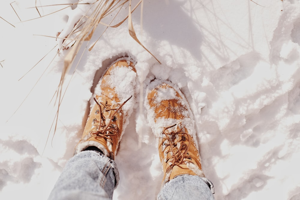 person in brown hiking shoes standing on snow covered ground