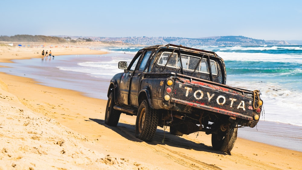black suv on brown sand near body of water during daytime