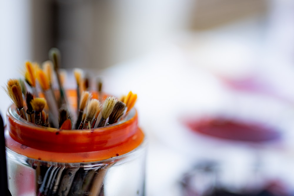 selective focus photography of paint brushes in clear glass jar