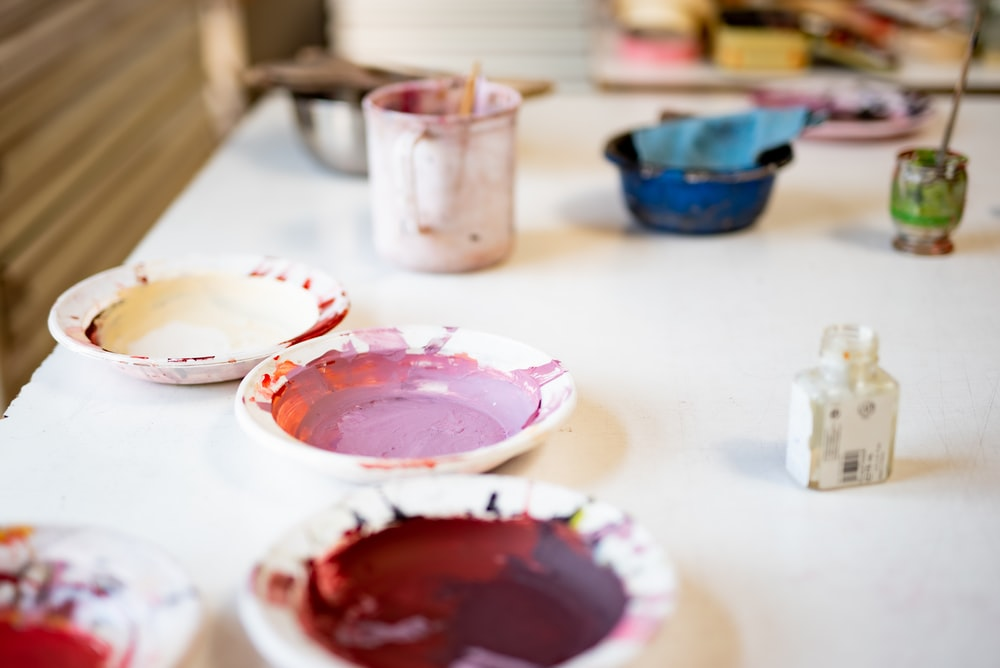 white and red ceramic mug on white table