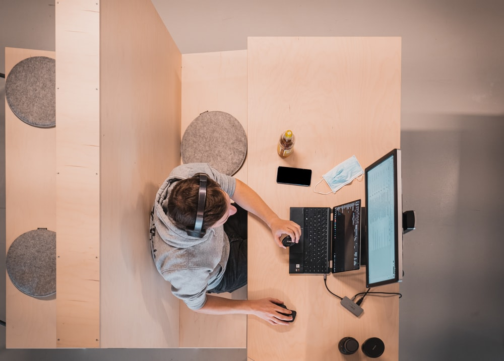 woman in blue shirt sitting on chair using laptop computer