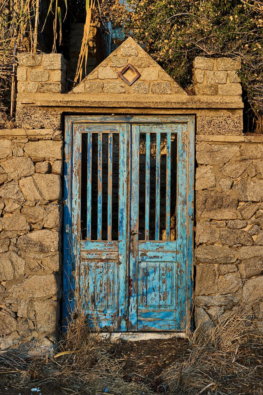 blue wooden door on brown brick wall