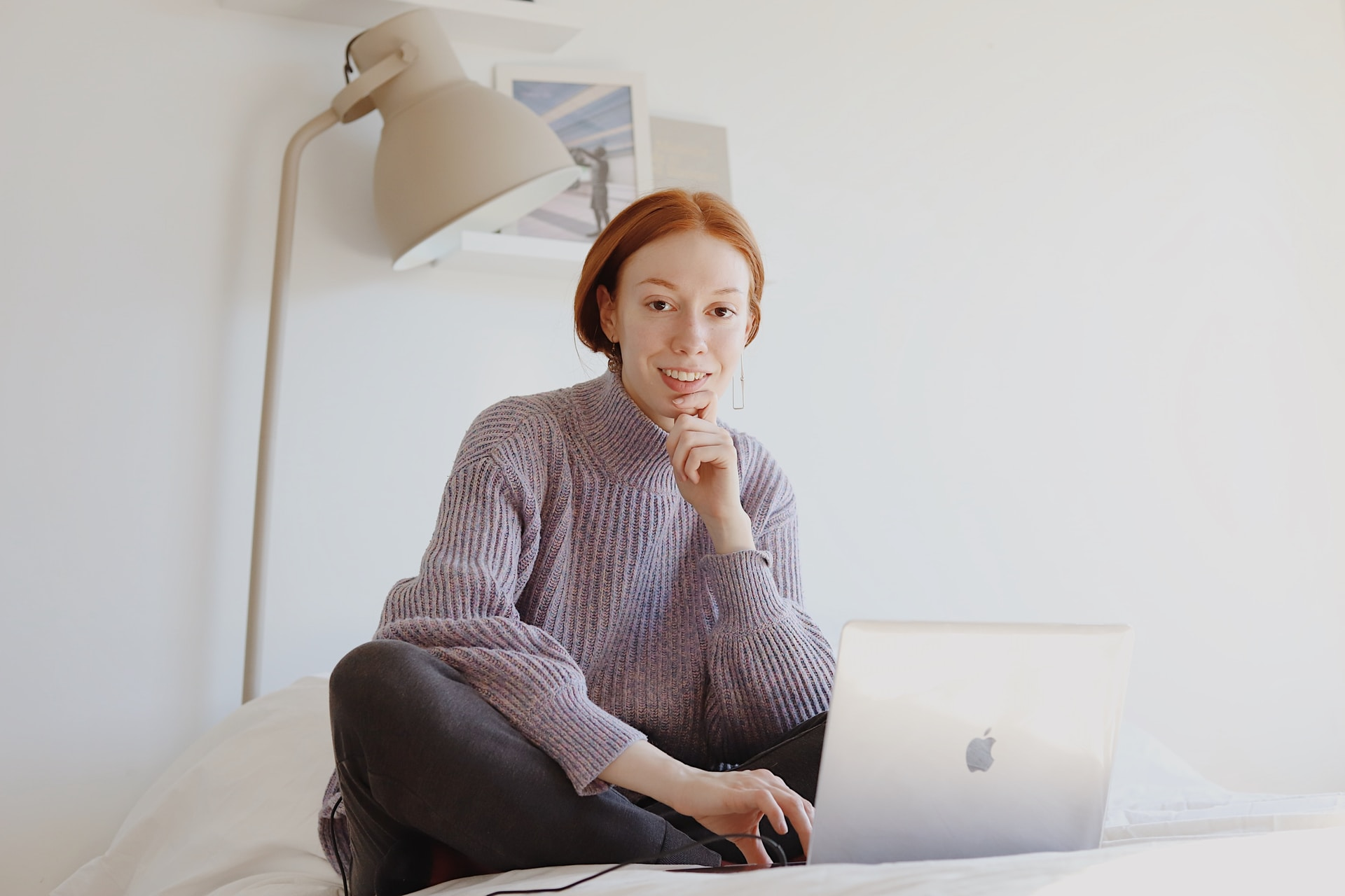 woman in gray sweater sitting on chair using macbook