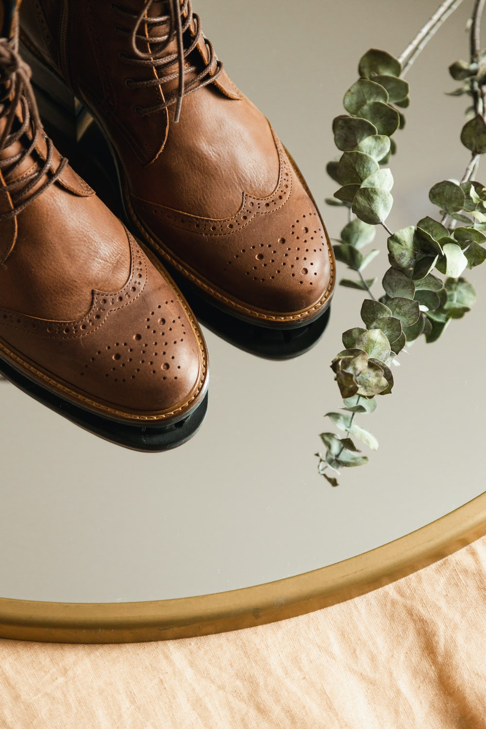 brown leather shoes on white table