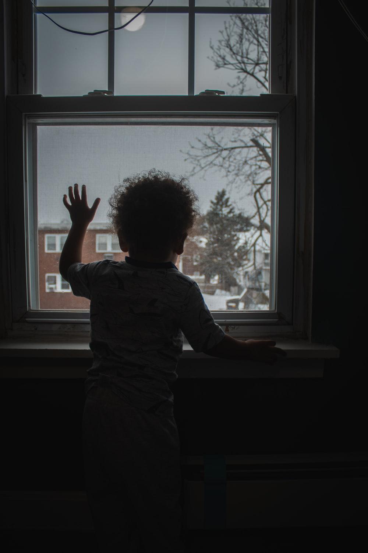 boy in blue shirt standing beside window