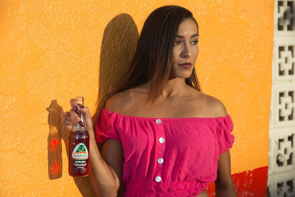 woman in pink off shoulder shirt holding plastic bottle