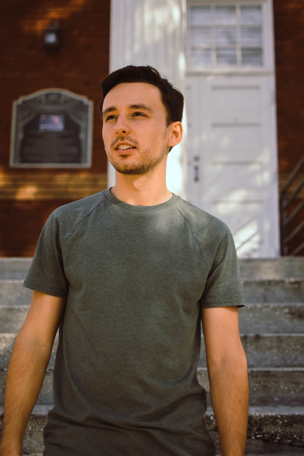 man in gray crew neck t-shirt standing near brown wooden wall during daytime