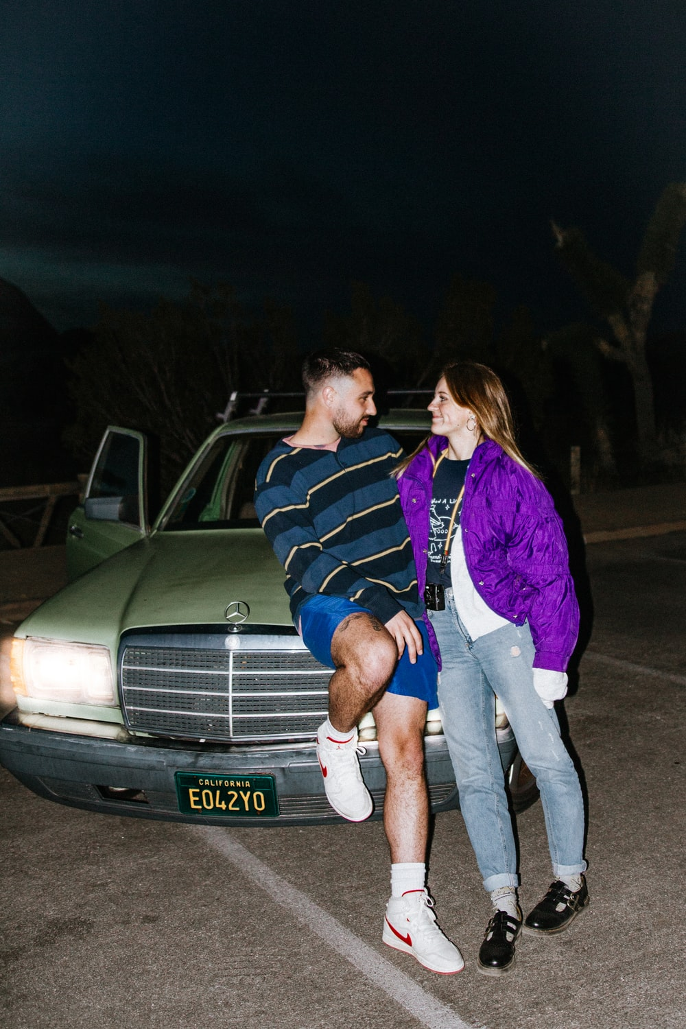 man and woman standing beside white car during night time