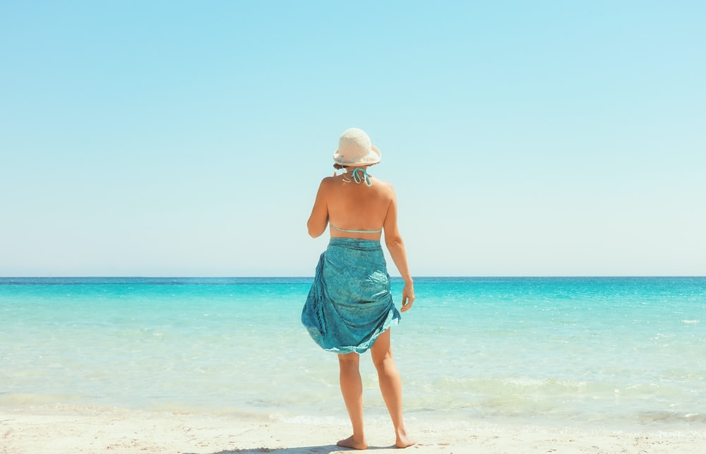 woman in blue skirt standing on beach during daytime