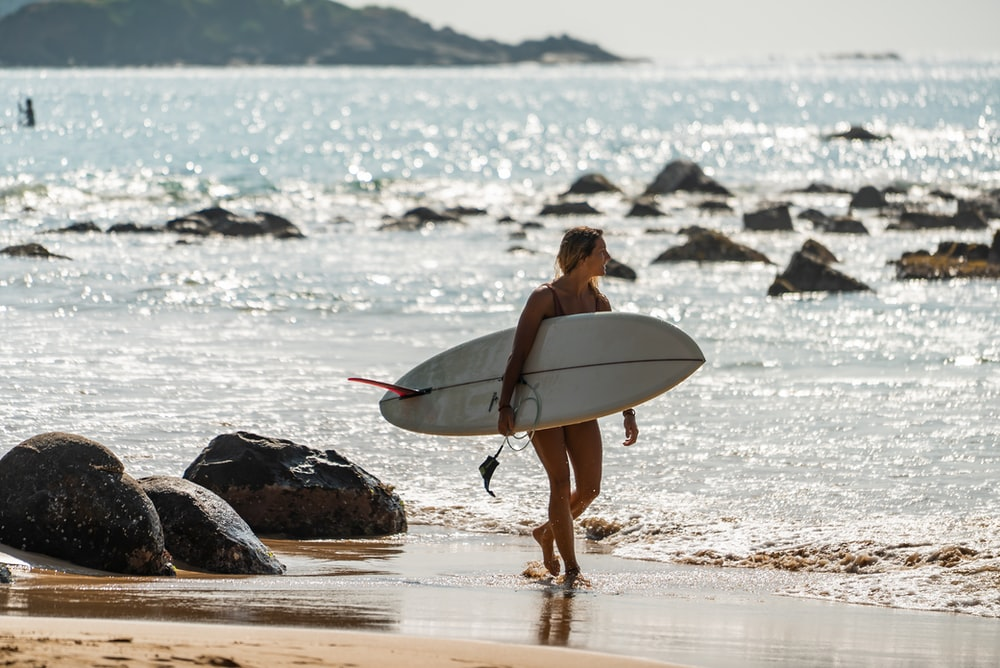 woman in black bikini holding white surfboard walking on seashore during daytime