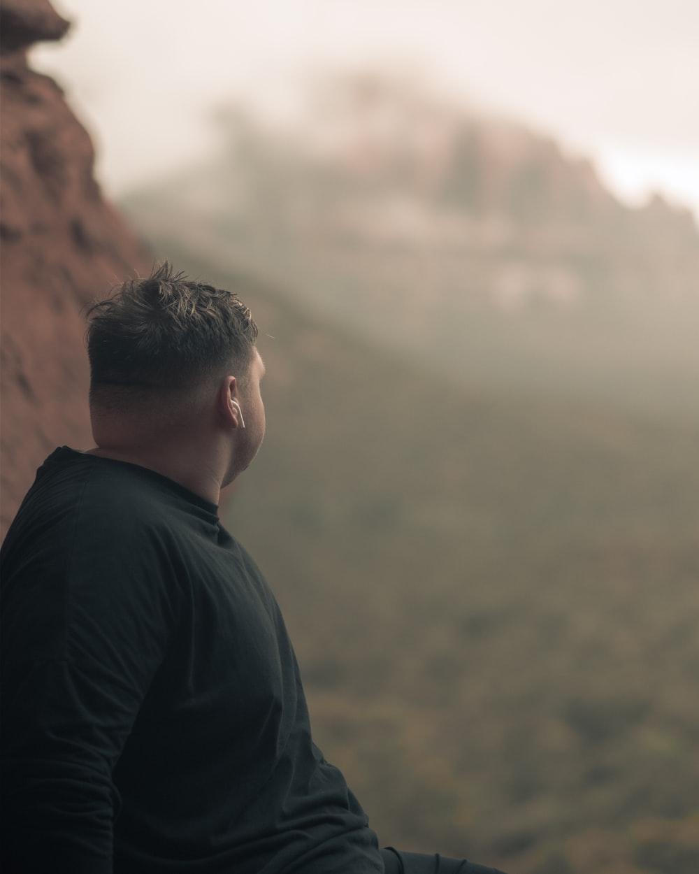 man in black long sleeve shirt standing on brown rock during daytime