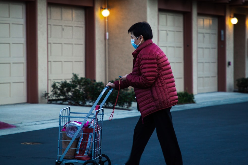 man in red and black striped hoodie and black pants riding on red and gray shopping