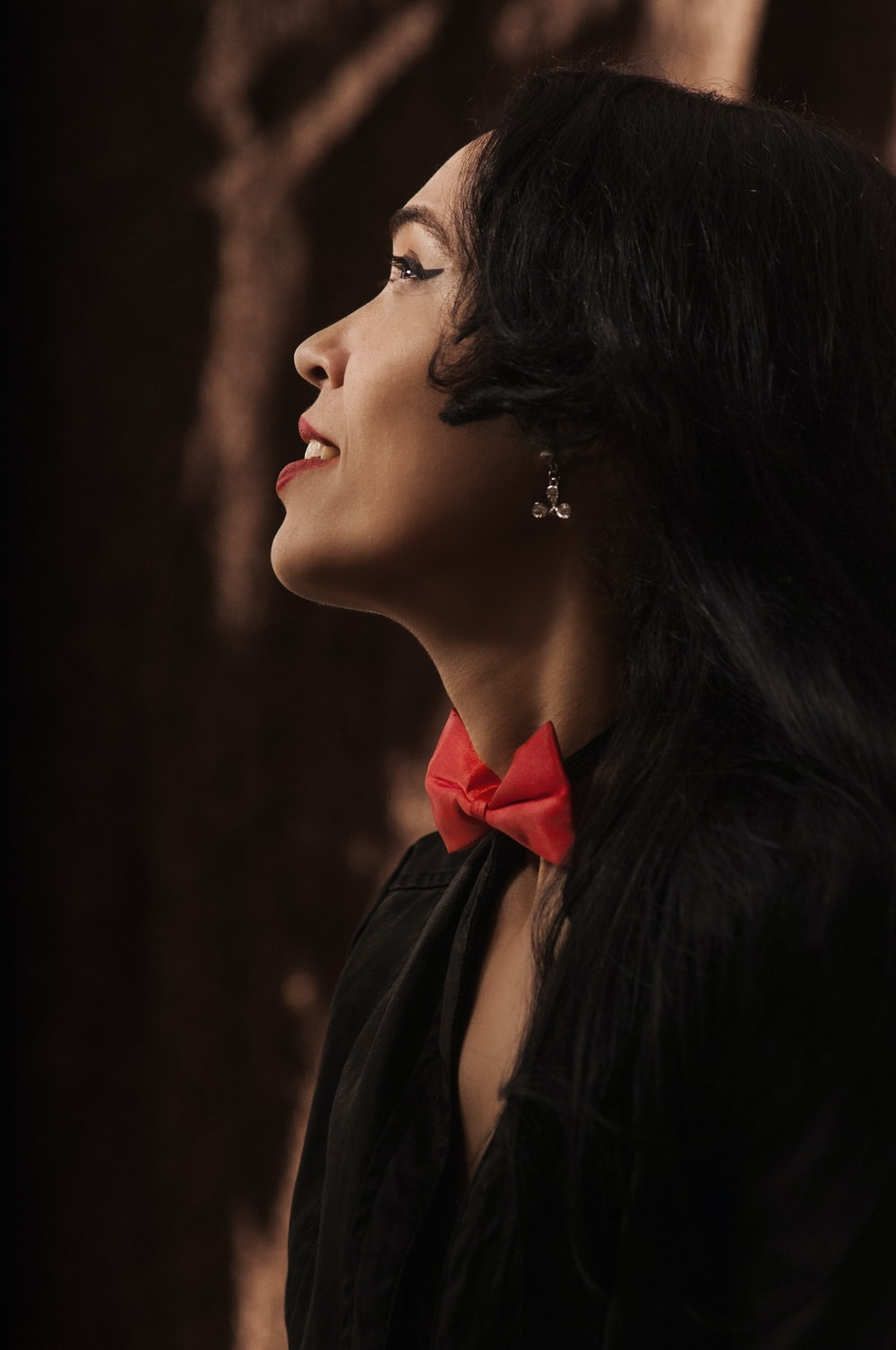 woman in black dress with red ribbon on her hair