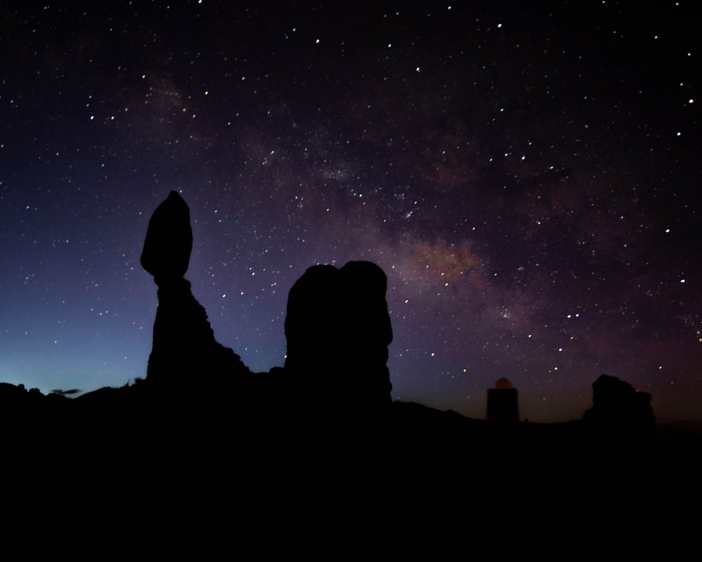 silhouette of person standing on rock formation under starry night