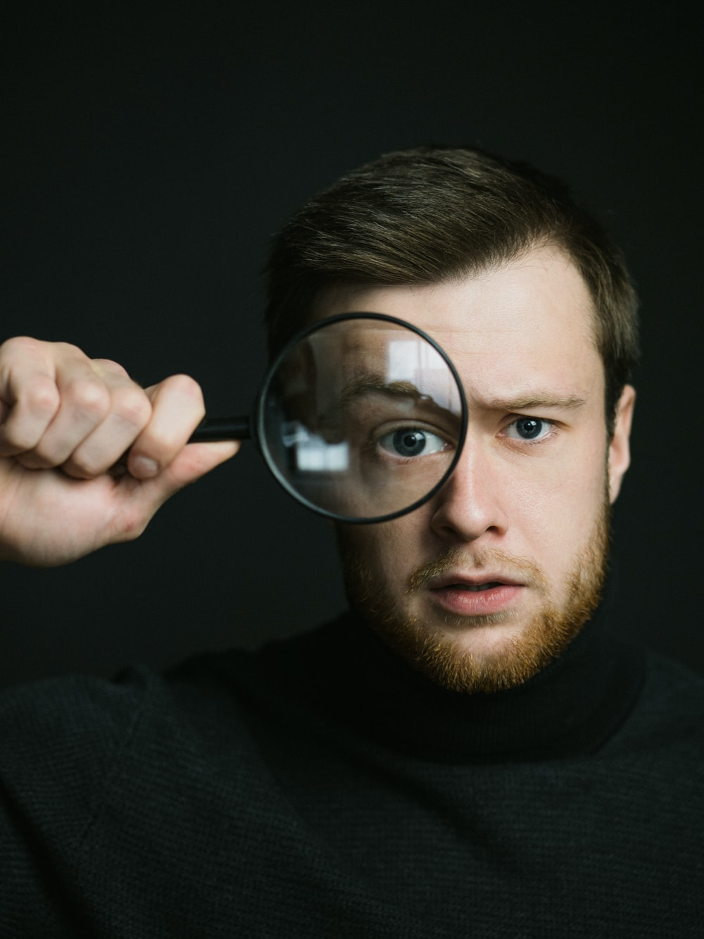man in black crew neck shirt holding magnifying glass