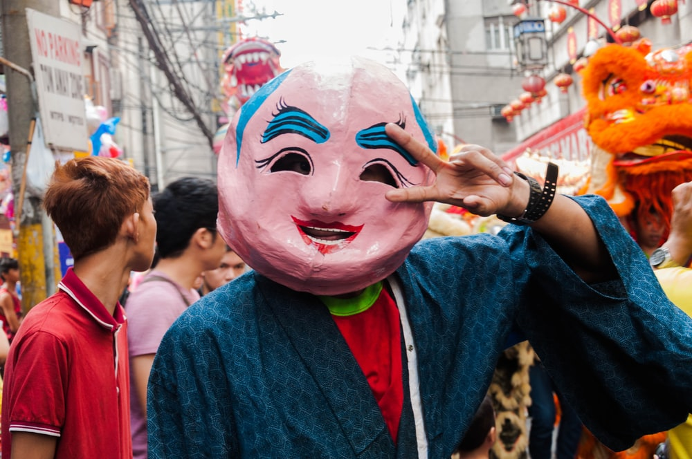 man in blue denim jacket with pink and white face mask