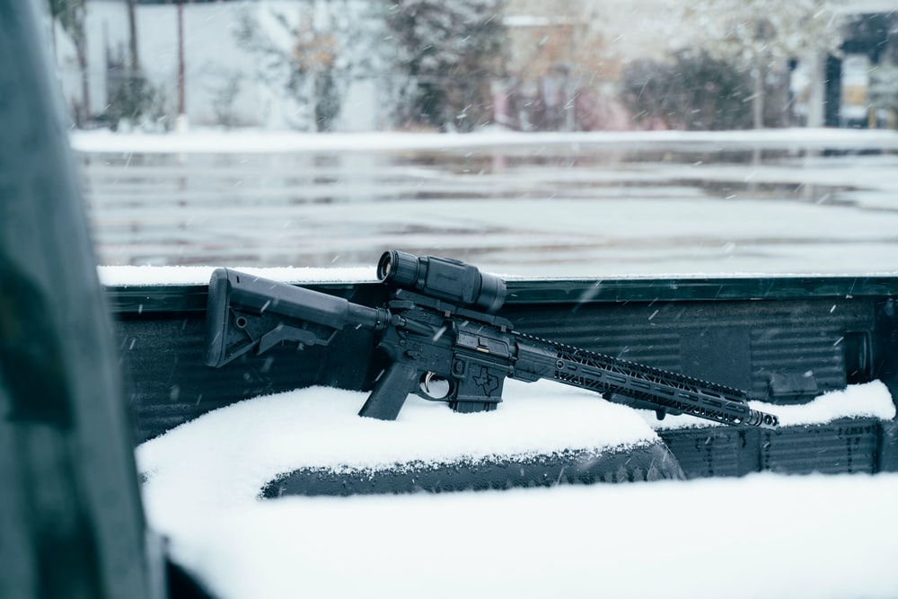 black rifle on snow covered ground during daytime