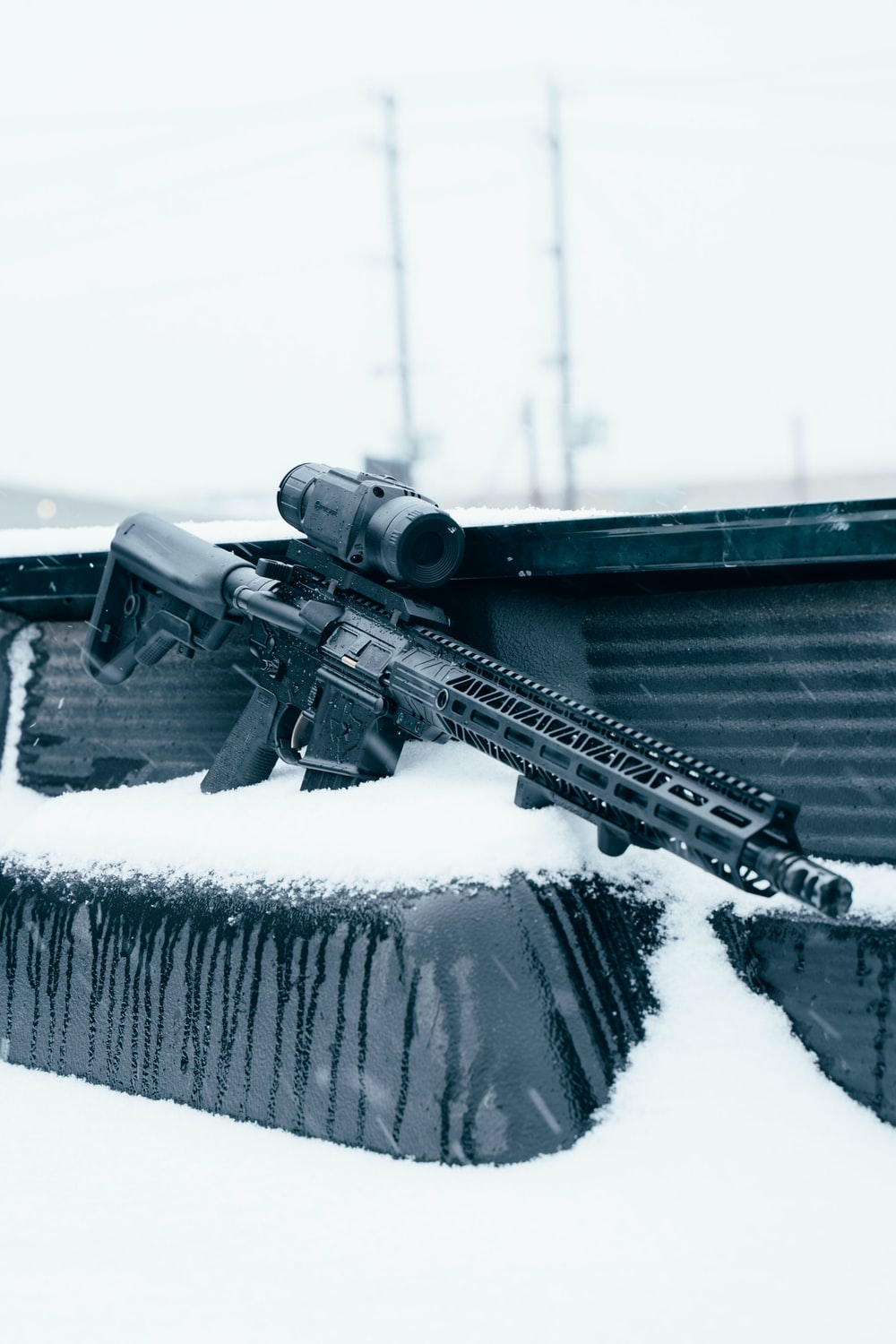 black assault rifle on snow covered ground