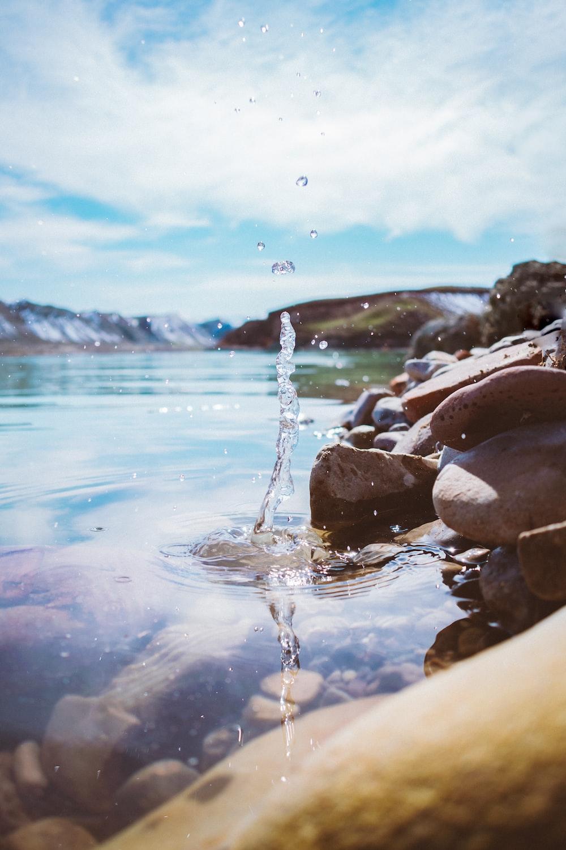 water splash on brown rocks during daytime