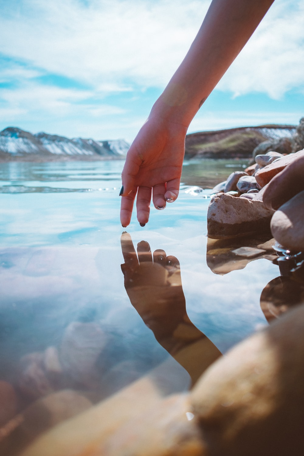 person with brown nail polish holding stones near body of water during daytime