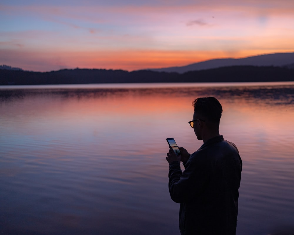 man in black jacket holding smartphone near body of water during sunset